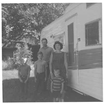 B&W picture of family (mom, dad, 3 boys) standing in front of Tee Pee trailer.