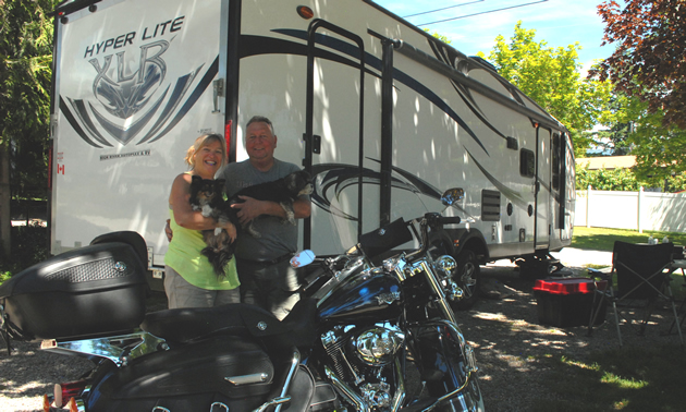 A couple each hold a small dog, standing in front of a dark purple Harley and in front of a new toy-hauler trailer.