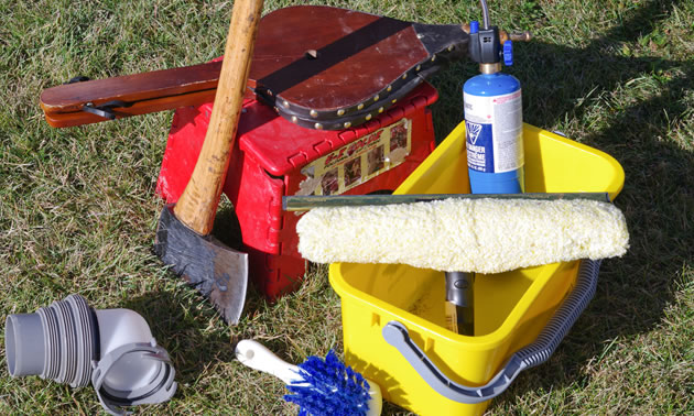 Shown are some of the author's essential items packed in his RV: a bucket, brush, bellows, an axe and a propane cylinder.