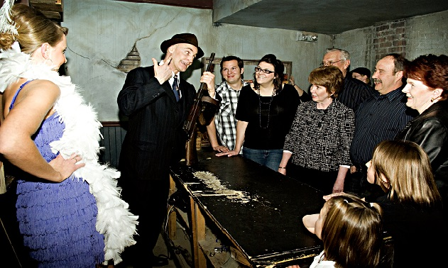 Actors in period costume take a group of guests through the Moose Jaw Tunnels, telling them a story of gangsters an prohibition.