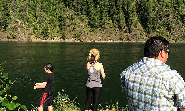 Eric Buckley, Nicole Lind and Will Buckley standing on a rock and fishing the Pend d'Oreille River in British Columbia