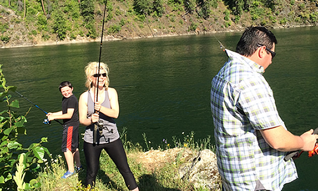 Eric Buckley, Nicole Lind and Will Buckley fishing the Pend d'Oreille River while Nicole's lure hooked the collar of Will's shirt