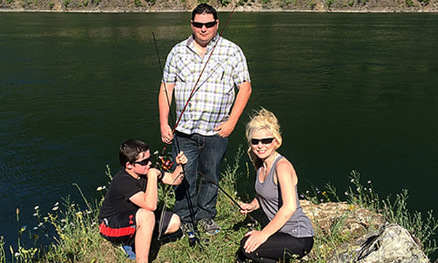 Eric Buckley, Will Buckley and Nicole Lind standing on a rockposing with fishing rods at the Pend d'Oreille River in British Columbia