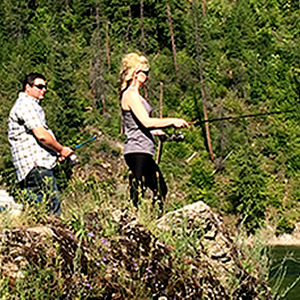 Will Buckley and Nicole Lind standing on a rock and fishing the Pend d'Oreille River in British Columbia