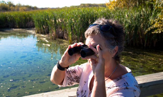 A lady looking through binoculars.