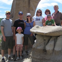 people standing next to limestone hoodoo formations on a summer day wearing casual attire