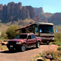 A red truck and brown RV are parked in front of Arizona's Superstition Mountains