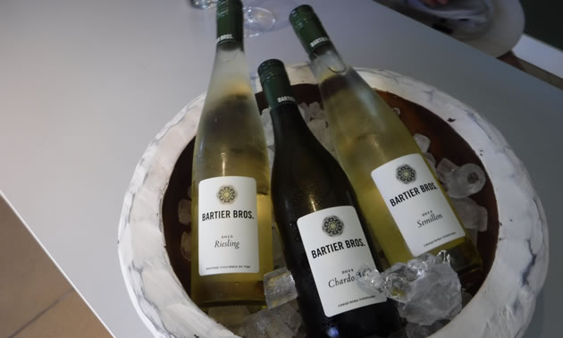 Bottles of white wines produced by Bartier Bros. are in a container on ice.