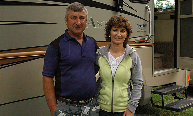 Middle-aged couple stand beside their motorhome.