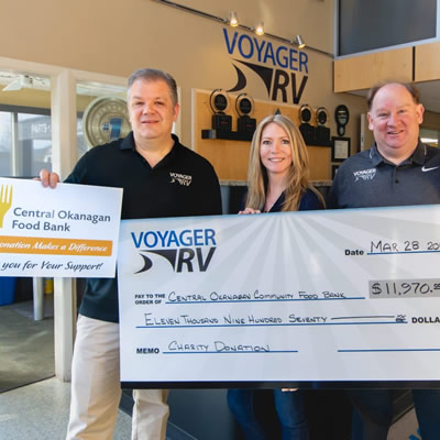 Voyager RV staff holding large cheques.