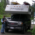 A man stands at the front of a black pickup with an adventure camper uploaded. It has kayaks on top.