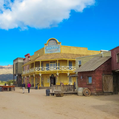 A streetscape of an Old Western town with a  large yellow hotel