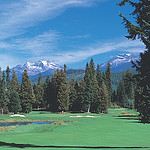 Scenic picture of the golf course in the forground, trees, mountains and ski in the background.