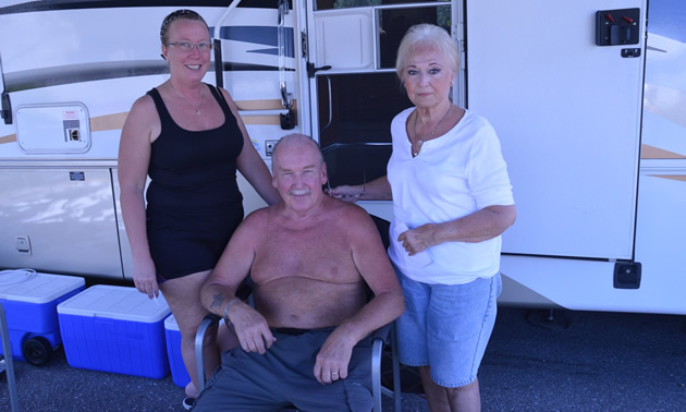 Two women standing, shirtless senior man sitting, with an RV unit behind them