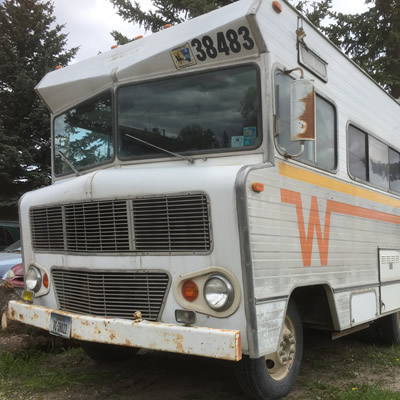 Winnebago motorhome with orange and yellow 'Flying W' logo on side.