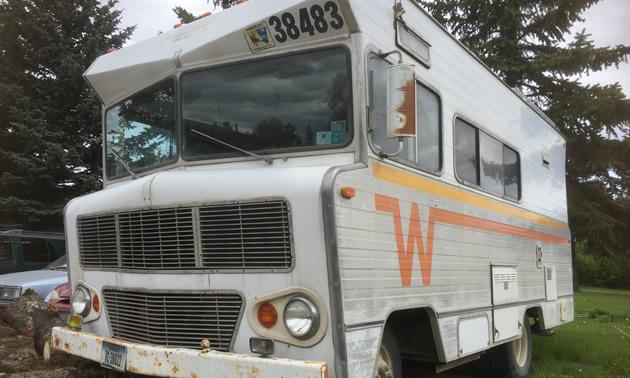 Winnebago motorhome with orange and yellow 'Flying W' logo on side.