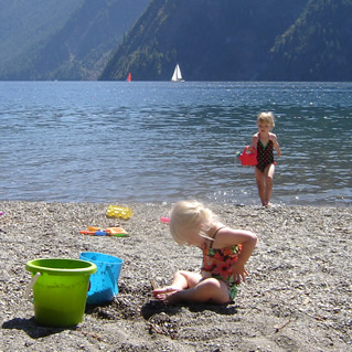 Two little blond girls playing on a beach