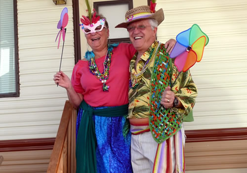 Stefan Sykut and Sharone O'Brien are dressed in bright Mardi Gras costumes.