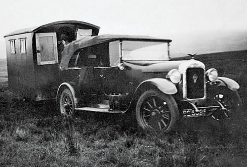 A black and white photo shows a car pulling a wooden travel trailer.