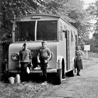 A black and white photo shows three children, including Stefan Sykut, in front of a wooden caravan.