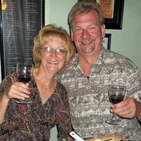 Sitting senior couple raise glasses of wine in a toast