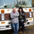 Jeanette wears a leather coat and stands next to Dennis in who wears a hoodie and jeans. Behind them is the brown and cream bumper of their flat-nose bus.