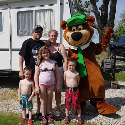 A family poses together with a Yogi Bear mascot.