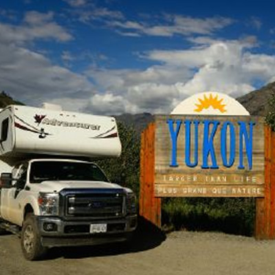 Truck camper parked beside sign.