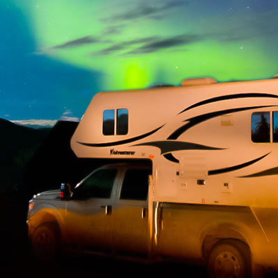 Picture of RV with aurora in background.