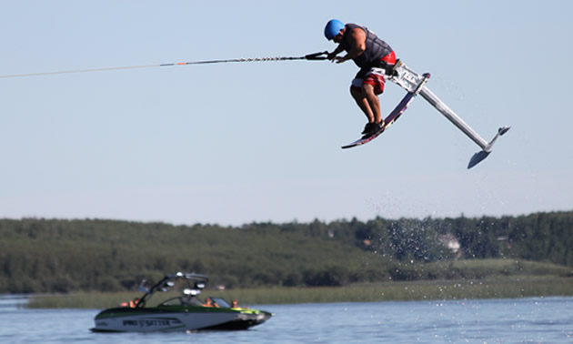 A person is flying through the air on an air chair above the lake water.