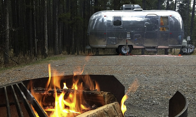 Picture of campfire in foreground, with silver Airstream trailer in background.