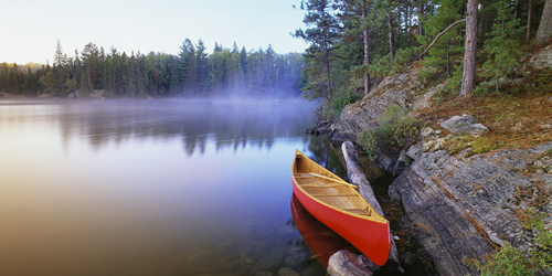 A canoe rests on Pinetree Lake, Algonquin Provincial Park, Ontario