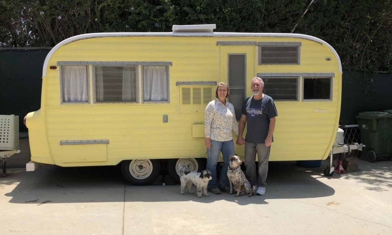 Couple with two dogs standing in front of a yellow vintage RV
