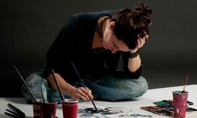 The artist Siobhan Humston sitting cross legged on the floor painting one of her pictures.