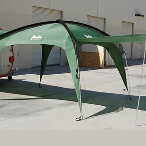 A green Cottonwood XLT shade shelter set up to join a teardrop trailer.