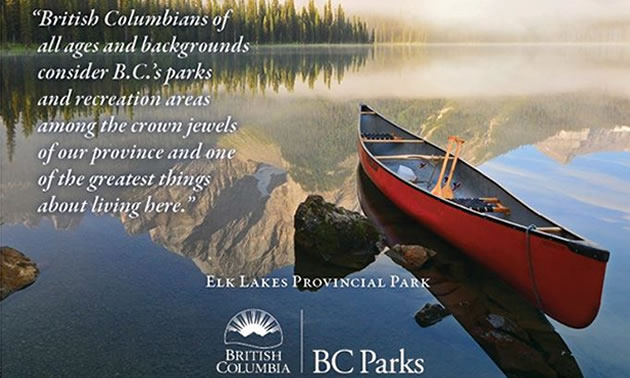 Picture of BC park, with red canoe sitting in fog-shrouded lake, mountain in background.