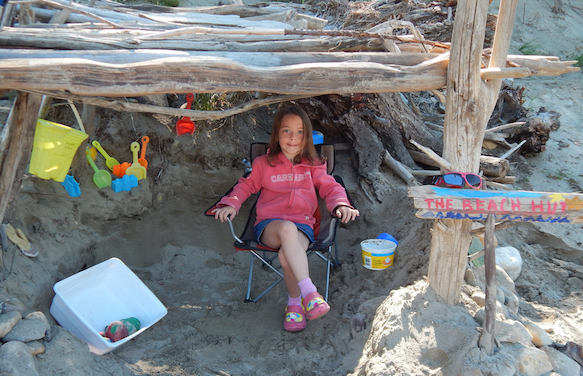 Kayden Gillard relaxing in a child sized lawnchair in a beach hut made out of drift wood.