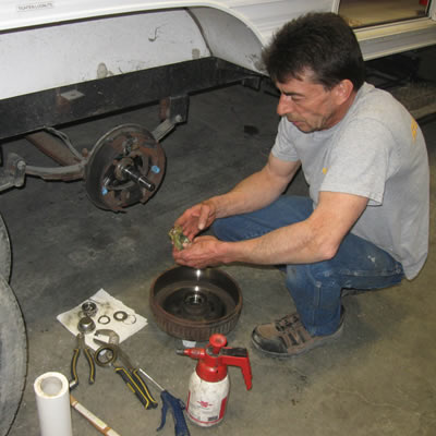 Lloyd Panchuk, an RV service technician with Runners RV in Cranbrook, B.C., works on repacking wheel bearings.