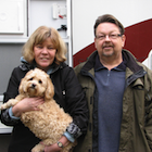 middle-aged couple standing in front of RV; woman holding a dog.