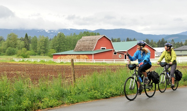 2 Bikers riding past a red barn.