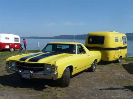 A restored black and yellow Boler trailer, towed by a black and yellow El Camino sits on display at a beachside parking lot.