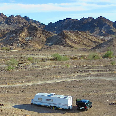 rv in the middle of a field with mountains around it
