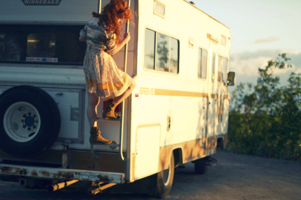 A young woman in a dress climbs down a ladder that is attached to the end of an RV.