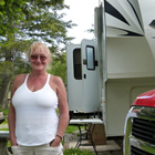 Photo of a lady in a white shirt standing in front of a red Dodge truck and a fifth wheel trailer.
