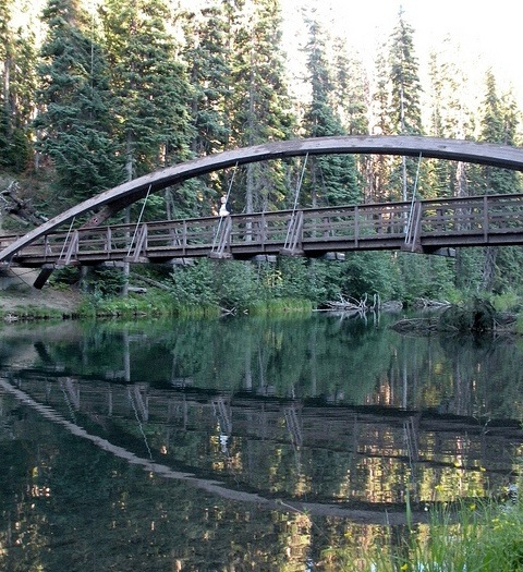 A photo of a bridge and its reflection in the water.