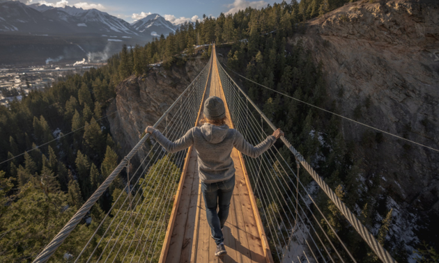lady walking on a suspension bridge