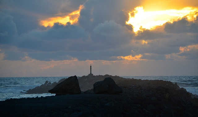 A lighthouse on the edge of a rock jutting out into the coast near Rockaway Beach, Oregon.  There is a black stormy sky, with one opening in the clouds showing light.