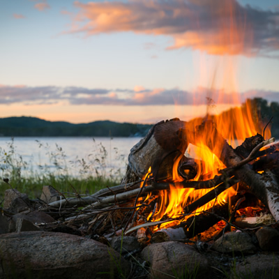 Close-up picture of campfire with sunset in the background.