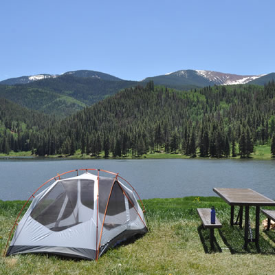 Scenic picture of tent, picnic table, with lake and mountains in background.