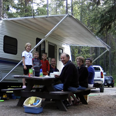 Picture of family camping beside RV.